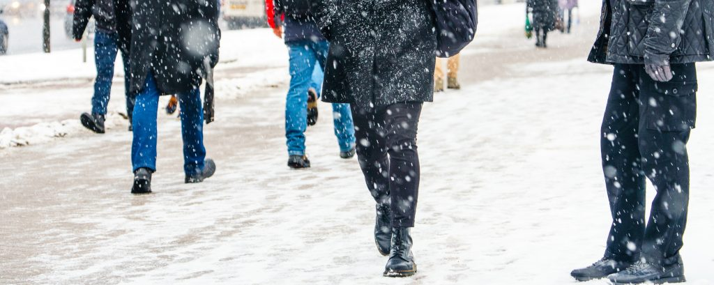 people walking on a snowy sidewalk