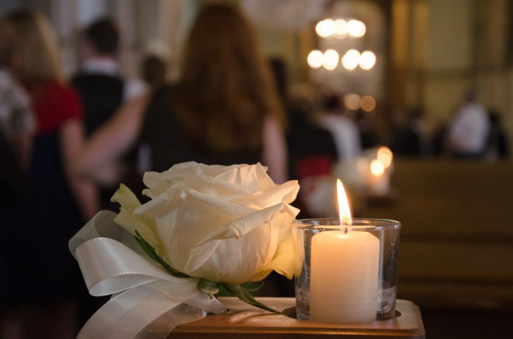 White rose and candle in a church