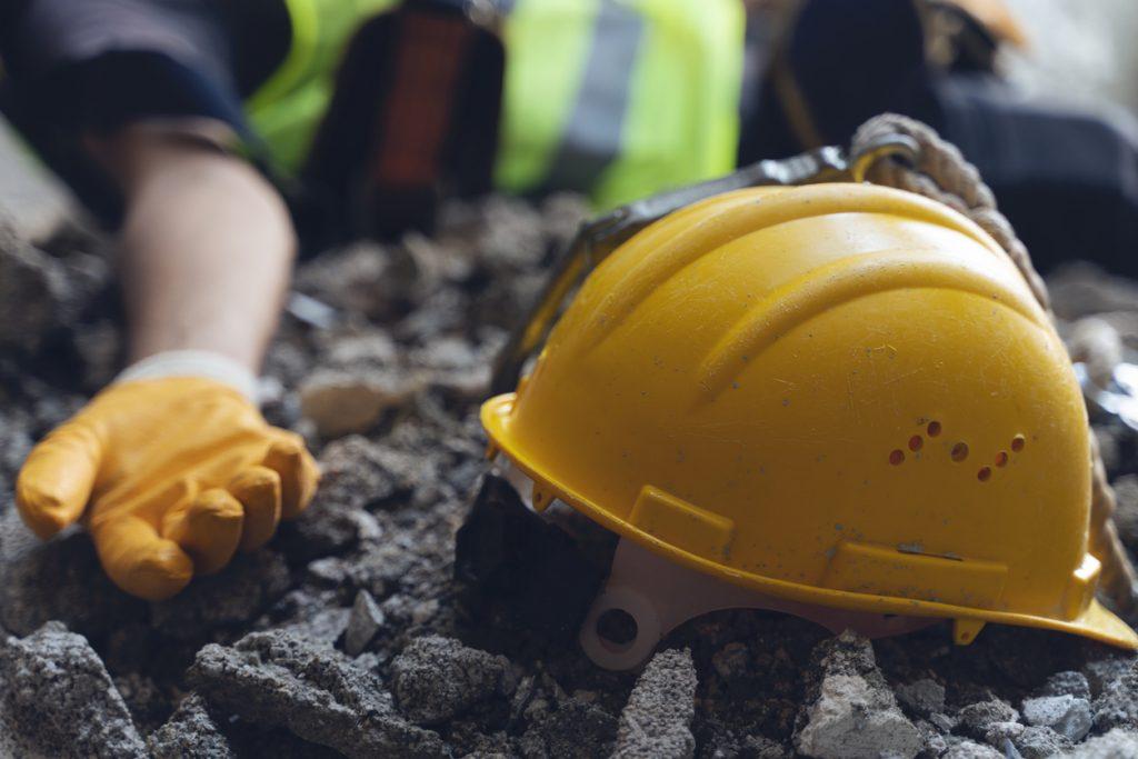 Injured construction worker next to hard hat
