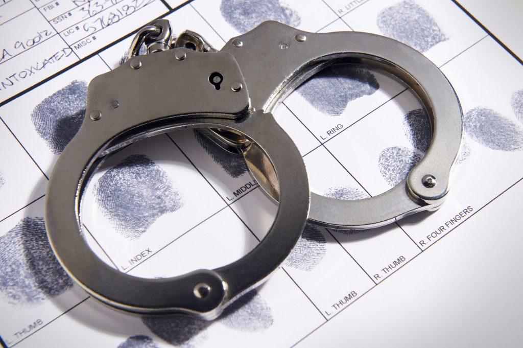 Handcuffs on top of a fingerprint chart